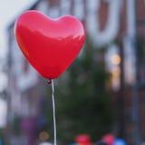 LED红色气球在forme心脏和心脏另外的剪影里在天空的在晚上 浪漫样式爱概念 图库摄影