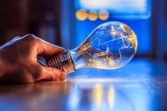 想法、启发和发明的时刻:手拿着一个LED电灯泡 免版税库存图片