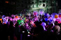 LED balloons people, holding many lighted balloons filled with toys and lights. Many people carrying LED lighted helium balloons lit by LED technology and filled royalty free stock photo