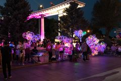 LED balloons people, holding many lighted balloons filled with toys and lights. Many people carrying LED lighted helium balloons lit by LED technology and filled stock photos