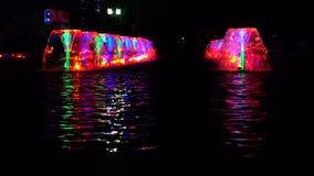 LED beleuchtete Mehrfarbenbrunnen an der Nacht und an der reflektierenden Wasserkräuselung Video 4K stock footage