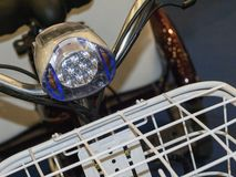 LED Bicycle Light. Bicycle LED headlight fixed on the bicycle handlebar near the front trunk Royalty Free Stock Photo