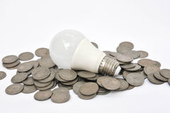 LED Bulb and coins Royalty Free Stock Photos