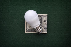 LED bulb and one hundred dollars bill Stock Image