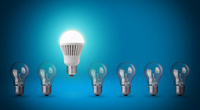 LED bulb. Row with light bulbs and LED bulb. Idea concept on blue background Royalty Free Stock Photo