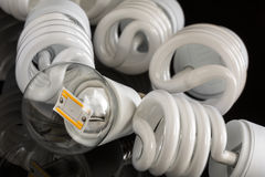 Led bulb between several CFL lamps Stock Photos