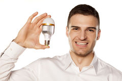 LED bulb. Smiling attractive young man, holding the LED bulb in his hand royalty free stock photos