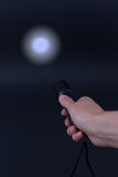 LED flashlight with a light beam in hand stock image