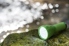 LED flashlight at waterside Royalty Free Stock Photo