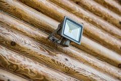 LED flashlight on a wooden log wall Stock Photo