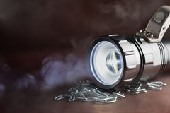 LED flashlight on a wooden table with a croak, in the smoke. Stock Photography