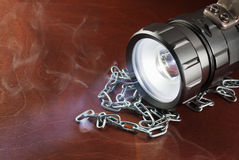 LED flashlight on a wooden table with a croak, in the smoke. Royalty Free Stock Photography