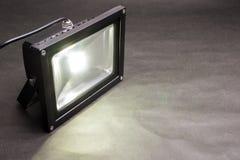 LED floodlight. One LED floodlight emitting on dark paper Royalty Free Stock Photography