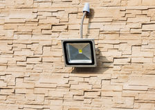 LED floodlight on wall of house. LED floodlight on wall of house covered with lite brown decorative slate stone wall surface Royalty Free Stock Images