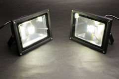 LED floodlights. Two LED floodlights emitting on dark paper stock photography