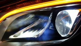 LED Headlight of a car Shining. Ecological led light of a car shining bright. Testing the lights of an auto. Auto engineer showing car parts stock video footage