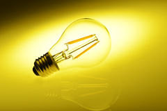 Led lamp. Bulb against  yellow background Royalty Free Stock Image