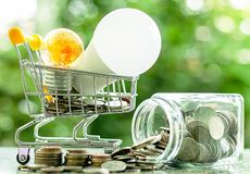 Led lamp and glowing light bulb in mini shopping cart or trolley. With money coins in the glass jar against blurred natural green background for finance, saving royalty free stock images