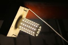 LED lamp mounted on wooden board to illuminate dark room. LED lamp mounted on a wooden board to illuminate a dark room royalty free stock images