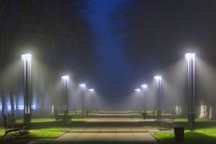 LED lanterns illuminated deserted alley in foggy night at autumn royalty free stock images