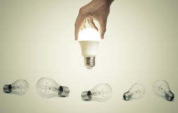 LED light bulb. Hand holding a turned on LED light bulb over old incandescent light bulbs / Using economical and environmentally friendly light bulb concept Stock Image