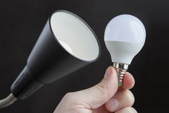 LED light bulb in human hand close to the luminaire. Royalty Free Stock Photo