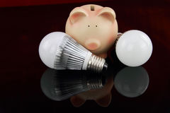 LED light bulbs with piggy bank. Over black background royalty free stock photo