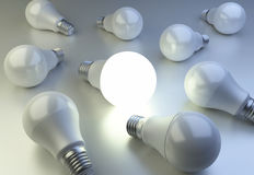 LED Light bulbs are scattered on the surface and one bulb shinin Stock Photos