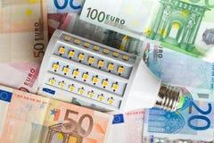 LED lightbulb with euro money Royalty Free Stock Image