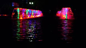 LED lit multicolor fountains at night and reflective water ripple. 4K video stock footage