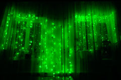 Led luminous garland with green lights on a dark background. Led luminous garland with green lights on a dark room wooden background Royalty Free Stock Photography