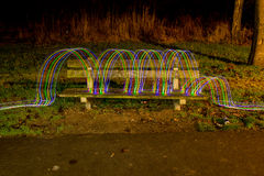 LED's jumping over a bench in a park. A bundle of LED's jumping of a bench, in a park, shot with long exposure Stock Photography