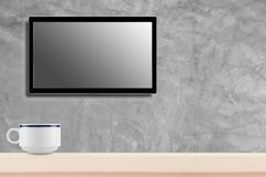 LED television screen mockup, blank hdtv on concrete wall with coffee cup in the room.  stock photo