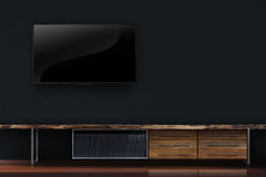 Led tv on black concrete wall with wooden table interior royalty free stock photo