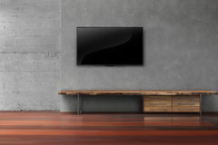 Led tvs on concrete wall with wooden furniture in empty living r Stock Photography