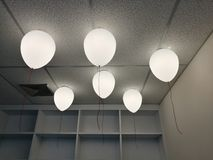 LED white creamy balloons burning fly away in the sky at night in the office room with blur white wood shelf background, holiday c Stock Images
