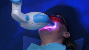LED whitening beauty cosmetic procedure for woman`s teeth in dentistry studio.