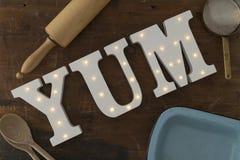 Leda-upplysta bokstäver som stavar YUM Surrounded, genom att laga mat hjälpmedel Royaltyfria Foton