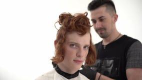Ledar- frisör Doing Haircut till en ung grabb med rött långt hår arkivfilmer