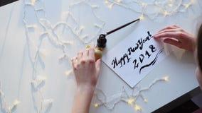 Ledar- kalligraffullföljande som drar feriekortet med färgpulver på det pappers- arket som sitter på tabellen med girlanden i sem stock video