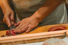 Ledar- kock för sushi som klipper slanka skivor av sashimien för tonfiskfisk i en dyr restaurang på Ginza Tokyo arkivbild