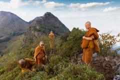 Ledar- munk för buddist som mediterar i berg Arkivbilder