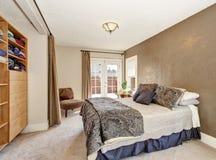 Ledar- sovrum med stor säng, den bruna väggen och ljus - bruna kabinetter Royaltyfria Foton