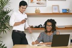 Ledare och anställd som arbetar på kontoret arkivfoto