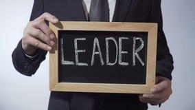 Ledare som är skriftlig på svart tavla, hållande tecken för businessperson, affärsidé lager videofilmer