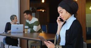 Ledare som använder den digitala minnestavlan, medan tala på mobiltelefonen 4k stock video