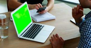 Ledare som använder mobiltelefonen och bärbara datorn på skrivbordet lager videofilmer