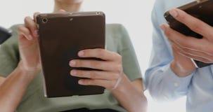 Ledare som använder mobiltelefonen och den digitala minnestavlan i kontoret 4k lager videofilmer