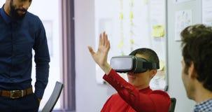 Ledare som använder virtuell verklighethörlurar med mikrofon på skrivbordet 4k stock video