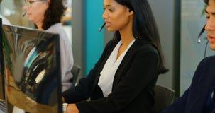 Ledare som arbetar med hörlurar med mikrofon på skrivbordet 4k lager videofilmer
